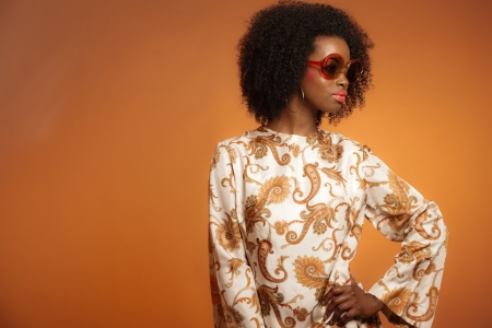 Retro 70s fashion african woman with paisley dress and sunglasses. Brown background. photo