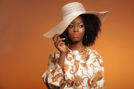 Retro 70s fashion afro woman with paisley dress and white hat. Brown background. photo