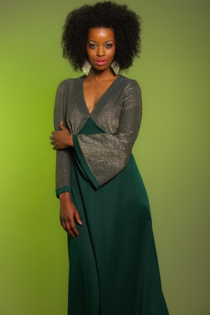Sensual retro seventies fashion afro woman with green dress. Green background. photo