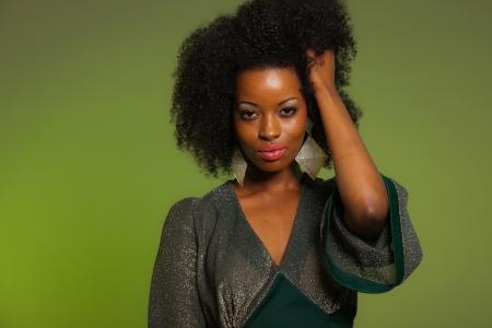 Retro dos anos setenta moda mulher afro sensual com o vestido verde. Fundo verde.