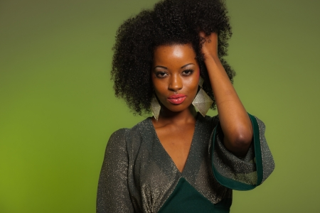 Sensual retro seventies fashion afro woman with green dress. Green background.