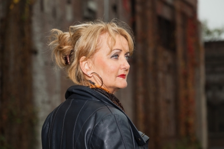 Pretty middle aged woman with blonde hair. Urban fashion. photo