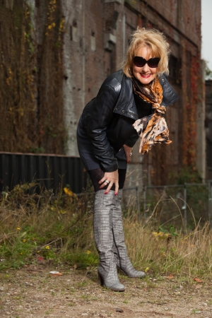 Pretty middle aged woman with blonde hair and black sunglasses. Urban fashion. photo