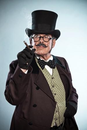 Styl vintage Dickens i mężczyzna z wąsem kapeluszu. Palenia cygara. Studio strzał. Zdjęcie Seryjne
