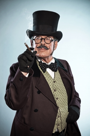 Vintage dickens style man with moustache and hat. Smoking cigar. Studio shot. photo