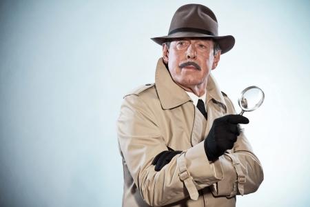 콧수염과 모자와 레트로 형사 남자. 돋보기를 들고. 스튜디오 샷. 스톡 콘텐츠