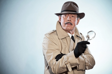 private investigator: Retro detective man with mustache and hat. Holding magnifying glass. Studio shot.