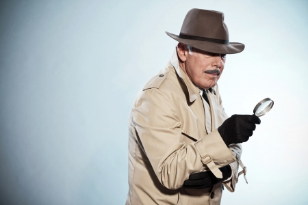 Retro detective man with mustache and hat. Holding magnifying glass. Studio shot.