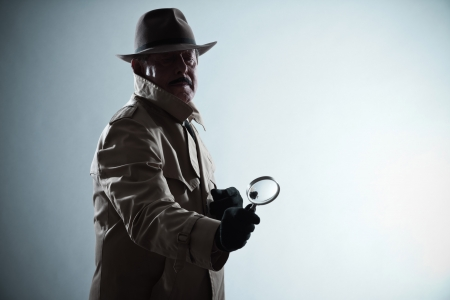 Silhouette of detective with mustache and hat. Holding magnifying glass. Studio shot.