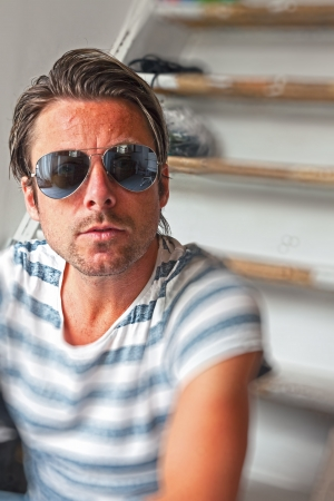 Casual fashion man with mirrored aviator sunglasses. Blonde hair. Indoor portrait. photo