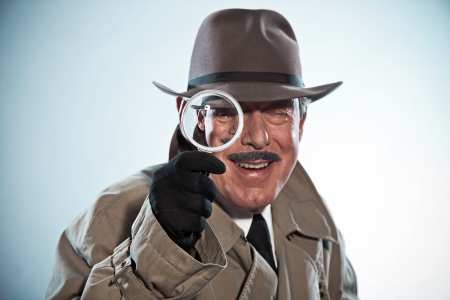 Vintage detective with mustache and hat. Looking through magnifying glass. Studio shot.