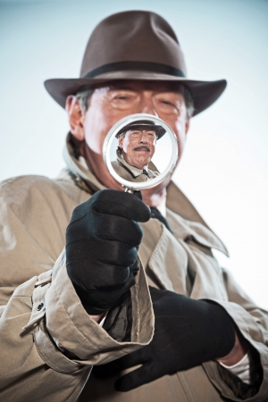 Vintage detective with mustache and hat. Looking through magnifying glass. Studio shot. photo