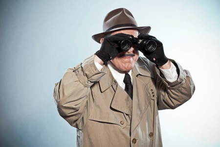 Vintage detective with mustache and hat. Looking through binoculars. Studio shot. photo