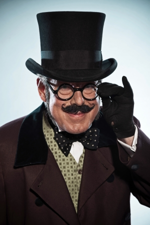 novelist: Funny vintage dickens style man with mustache and hat. Wearing glasses. Studio shot. Stock Photo