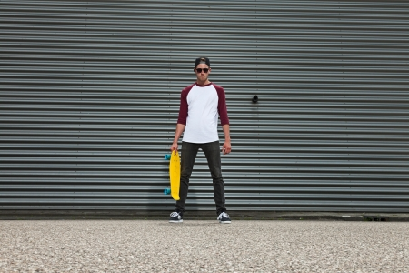 ni�o en patines: Cadera fresca skater moda urbana con gorro de lana en la calle en frente de la pared de hierro.