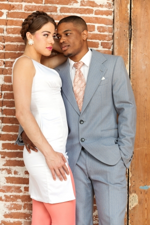 Vintage fashion romantic wedding couple in old urban building. Mixed race. Stock Photo