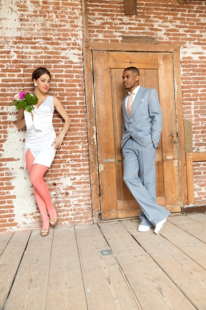 Vintage fashion romantic wedding couple in old urban building. Mixed race. photo