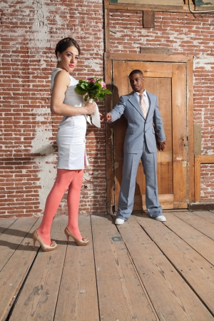 Vintage fashion romantic wedding couple in old urban building. Holding hands. Mixed race. photo