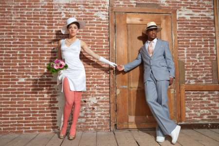 Vintage jazz fashion sexy wedding couple in old urban building. Mixed race. Wearing a hat. photo