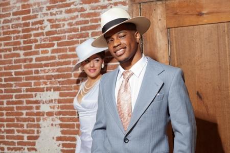 Jazz casal casamento moda retro no antigo prédio urbano. Noivo em foco. Mestiça. Vestindo um chapéu.