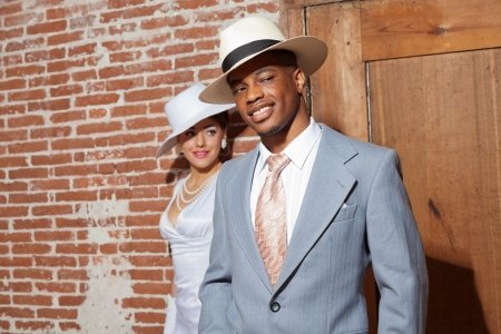Retro jazz fashion wedding couple in old urban building. Groom in focus. Mixed race. Wearing a hat.