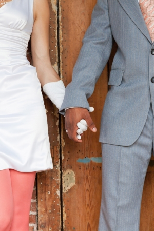 Closeup of holding hands of stylish wedding couple. Mixed race. photo