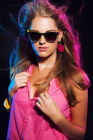 Sensual retro 80s fashion disco girl with long blonde hair and sunglasses. Black background.