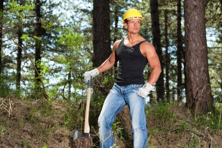 lumberjack shirt: Muscled lumberjack with black shirt and axe in forest. Wearing yellow safety helmet. Stock Photo