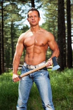 leñador: Sin camisa hombre musculoso físico leñador con el hacha en el bosque.