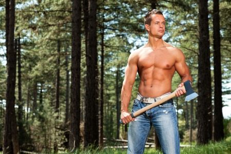 six packs: Shirtless muscled fitness lumberjack man with axe in forest.