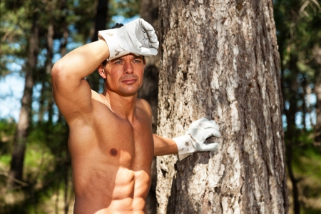 Shirtless muscled fitness man with working gloves in forest. Resting and staring. photo