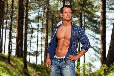 Good looking muscled fitness man with blue lumberjack shirt in forest. photo
