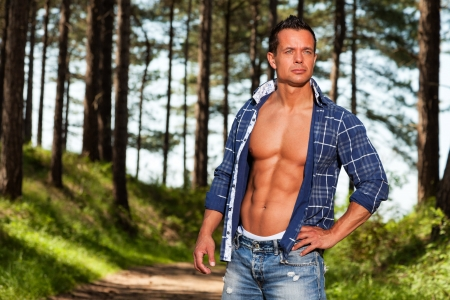 jungle gyms: Good looking muscled fitness man with blue lumberjack shirt in forest.