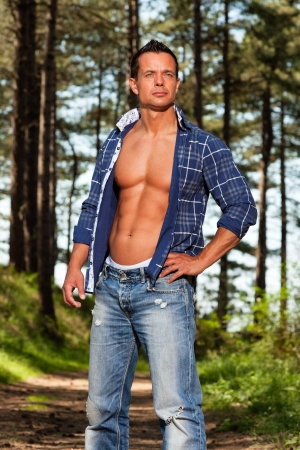 Good looking muscled fitness man with blue lumberjack shirt in forest.