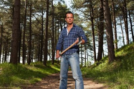 lumberjack shirt: Handsome strong lumberjack man holding axe. Wearing blue shirt. Standing in forest.