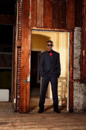 Retro fashion afro american groom wearing black suit and tie and sunglasses. Interior of old house.