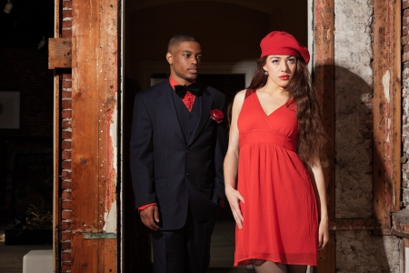 Vintage fashion mixed race wedding couple wearing black suit and red dress. Interior of old house. photo