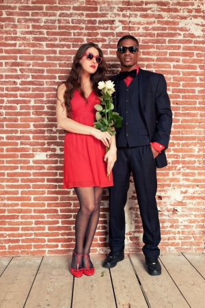 Urban cool retro fashion mixed race wedding couple wearing black suit and red dress and sunglasses.