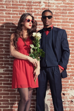 Urban cool retro fashion mixed race wedding couple wearing black suit and red dress and sunglasses. photo