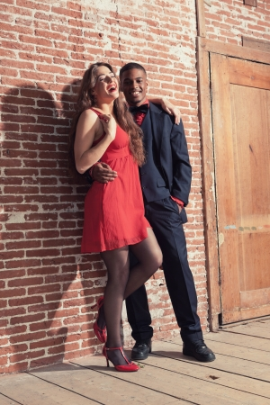 Urban cool vintage fashion mixed race wedding couple wearing black suit and red dress. photo