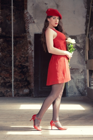Sensual sexy bride wearing red dress and hat standing in old house holding flowers. Stock Photo - 21064339