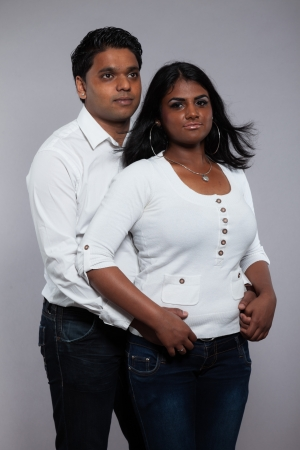 Young romantic indian couple. Wearing white shirt and jeans. Studio shot against grey. photo