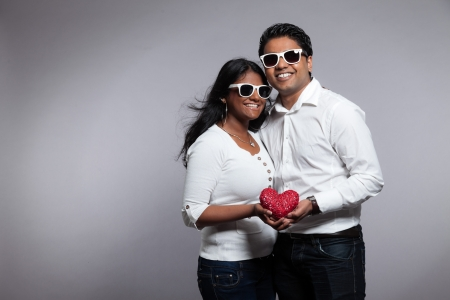 Romantic indian couple holding red heart. Wearing white shirt and sunglasses. Studio shot against grey. photo