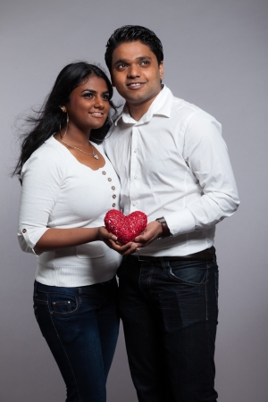 Romantic indian couple holding red heart. Wearing white shirt and jeans. Studio shot against grey. photo