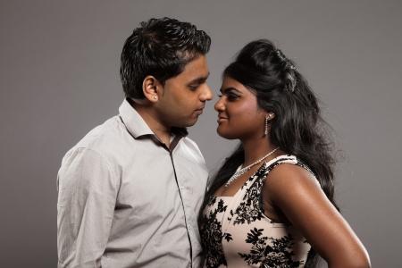 Fashionable passionate indian couple. Studio shot against grey. photo