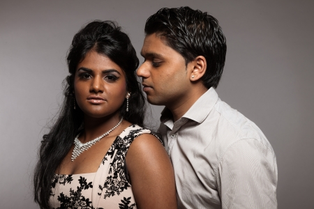 Fashionable passionate indian couple. Studio shot against grey. photo