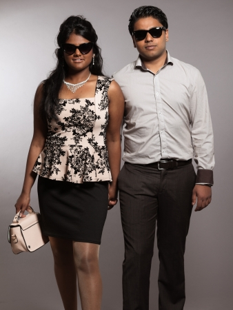 Fashionable indian couple walking towards camera. Wearing retro black sunglasses. Studio shot against grey. photo