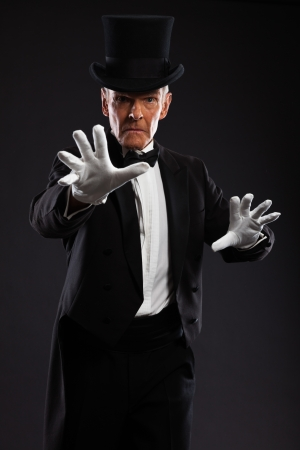 Magician making mysterious gestures  Wearing black suit and hat  Studio shot against black  photo