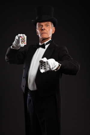 Magician with black suit and hat holding set of cards  Studio shot against black  photo