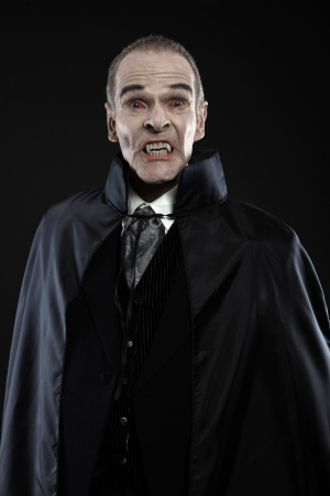 Dracula with black cape showing his scary teeth. Vamp fangs. Studio shot against black. Stock Photo - 21413403